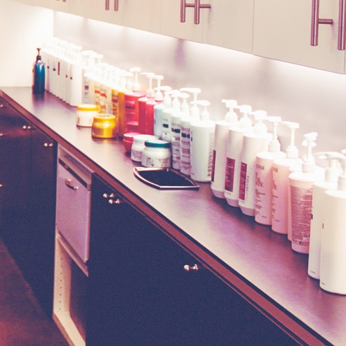 A row of hair shampoo and conditioner.